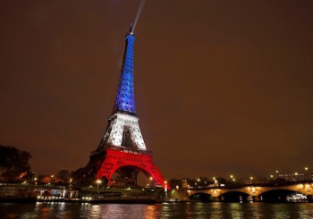 The Eiffel Tower is lit with the blue, white and red colours of the French flag in Paris, France, November 16, 2015, to pay tribute to the victims of a series of deadly attacks on Friday in the French capital. REUTERS/Benoit Tessier