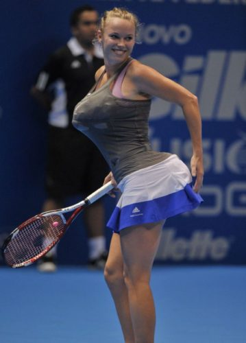 Danish tennis player Caroline Wozniacki impersonates Serena Williams by carrying towels under her clothes simulating bigger breasts and bottom, during an exhibition match against Maria Sharapova of Russia at the Ibirapuera Gymnasium in Sao Paulo, Brazil, on December 7, 2012. AFP PHOTO/Yasuyoshi CHIBAYASUYOSHI CHIBA/AFP/Getty Images